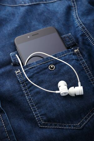smartphone mobile in Blue jeans shirt pocket with black screen and white earphones