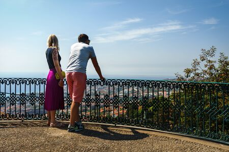 Cute couple on date looking on the Atlantic ocean, Funchal, Madeira, October 10, 2019 에디토리얼