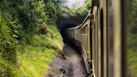 restored Steam locomotive train enters tunnel in picturesque green nature surround 스톡 콘텐츠