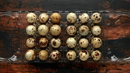 Quail eggs in transparent plastic container on wooden table. 스톡 콘텐츠 - 137851887