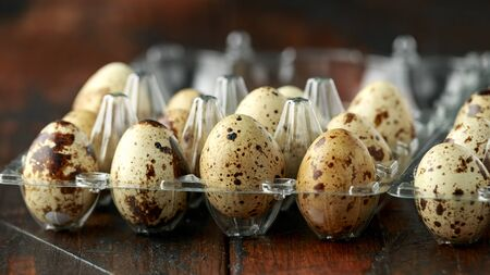 Quail eggs in transparent plastic container on wooden table.