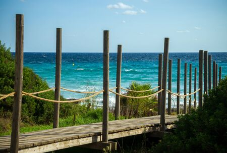 wooden decking leading to Santo Tomas beach in Menorca seascape with beautiful view of Mediterranian sea, Spain.