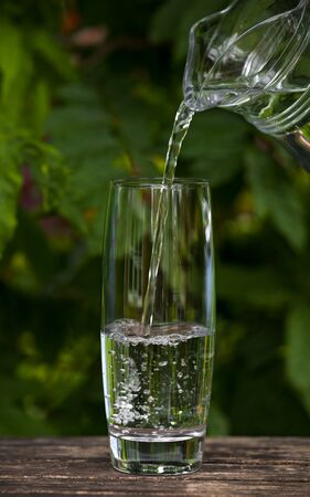 pouring Glass of clear water from jug on nature background.