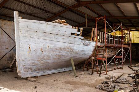 an old lobster fishing boat restoration in workshop.