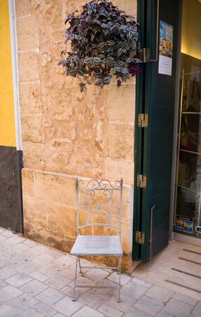 antique chair at shop front on old streets of Ciutadella, Menorca, Spain, September 12 2016. 스톡 콘텐츠 - 139727012