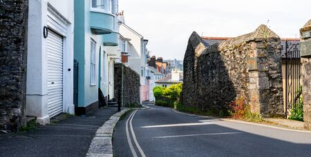 Narrow alley along colorful buildings, tall stone wall architecture, British riviera, Devon, United Kingdom, May 3 2018. 스톡 콘텐츠 - 139726966