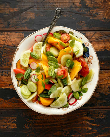 vegetarian vegan salad with crystal lemon cucumbers, cucamelon, radishes and orange tomato. Healthy food concept.