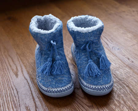 Knitted wool slippers, boots with warm plush insoles and pompons.