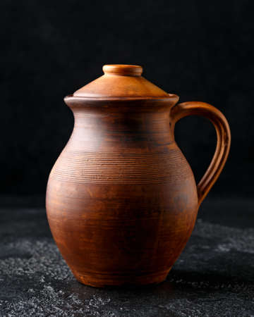rustic handmade brown clay jug with lid on black background.