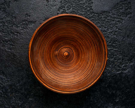 rustic handmade brown clay bowl plate on black background.