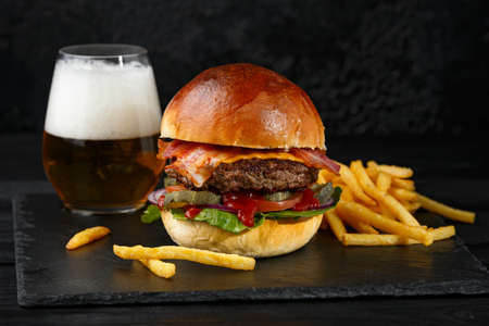 big tasty classic beef cheeseburger, french fries potato chips served on black slate board and beer ale in glass.