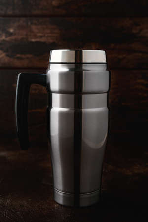 Travel Tumbler hot or cold drinks mug cup Stainless Steel Insulated Flask on wooden background.