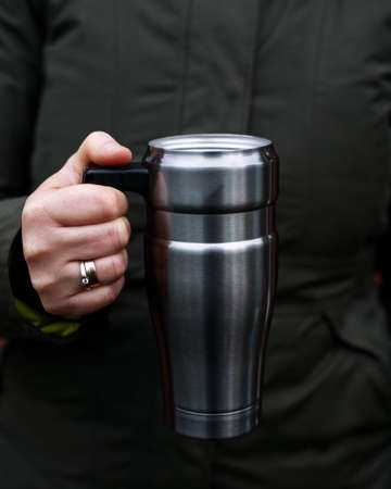 Young woman holding travel Tumbler stainless Steel mug with hot drink, reusable Insulated Flask on winter day,. Refuse, reduce, recycle and zero waste concept. Ecology.