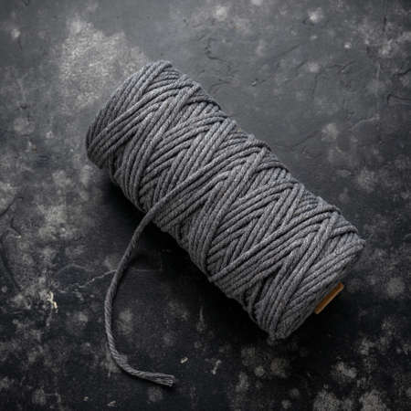 natural cotton gray macrame cord rope on bobbin for DIY creative activity on dark background.