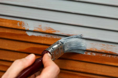 man's hand painting wooden panel door with a brush in lead gray color.
