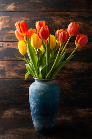 Red and yellow Tulip flowers in blue vase on wooden table spring celebration concept