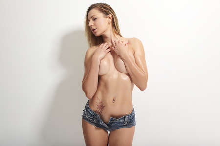 nude pose: topless girl in blue shorts Stock Photo