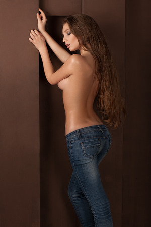 topless jeans: sexy topless woman in jeans, in oil, stands near wall, fashion shoot