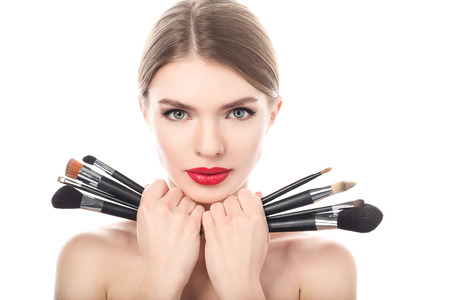 make up brush: Portrait of the beautiful woman with make-up brushes near attractive face. Adult girl posing over white background