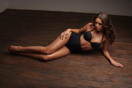 sexy young girl: Горячая сексуальная девушка лежала на деревянном полу в черном белье, брюнетка Фото со стока