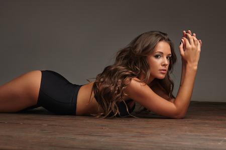 niñas en ropa interior: caliente chica sexy acostado en el piso de madera en ropa interior negro, morena Foto de archivo