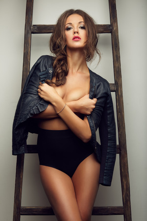 topless brunette: beautiful sexy woman topless in leather jacket near the ladder, in boots