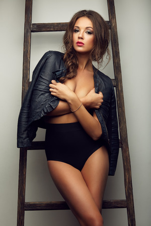 naked girl body: beautiful sexy woman topless in leather jacket near the ladder, in boots