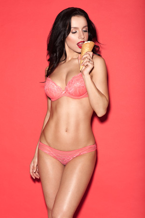 ice cream woman: sexy woman in lingerie on a red background eating ice cream Stock Photo