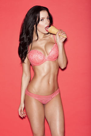 woman with ice cream: sexy woman in lingerie on a red background  eating ice cream