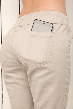 booty: smart phone in a pocket pants, beautiful girl with sexy booty on the background of wooden planks