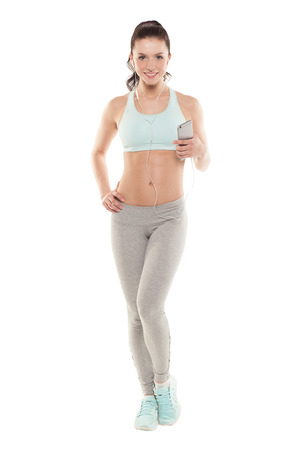 fitness girl with a smartphone on a white background, enjoys sports training, gym workout photo