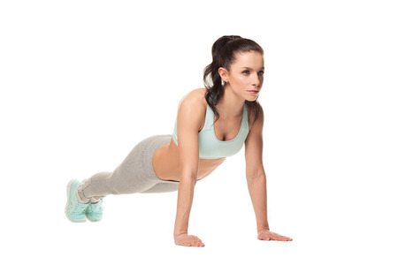 athletic woman doing push-ups on a white background. Fitness model with a beautiful, athletic body photo