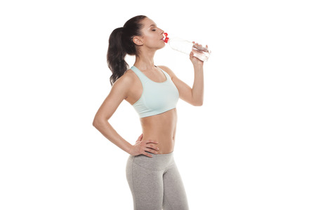 Sporty girl drinking water from a bottle after a workout, fitness training, isolated on white background photo
