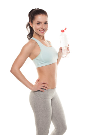Sporty girl drinking water from a bottle after a workout, fitness training, isolated on white background Stockfoto