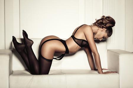 beaux seins: femme sexy en lingerie noire séduisante assis sur un canapé en bas