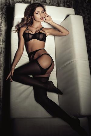 femme noire nue: femme sexy en lingerie noire séduisante couchée sur un canapé dans les bas