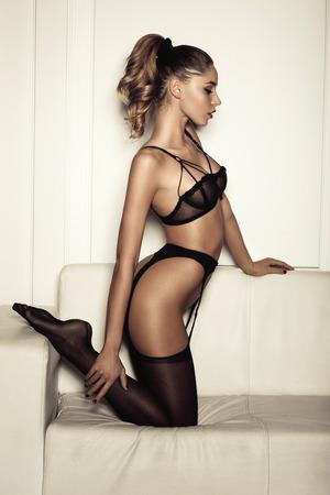 mujer desnuda sentada: mujer sexy en ropa interior negro seductora sentada en un sofá en medias