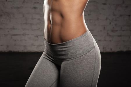 cuerpo femenino: Fitness mujer femenina con cuerpo musculoso, hacer sus ejercicios, abdominales, abdominales