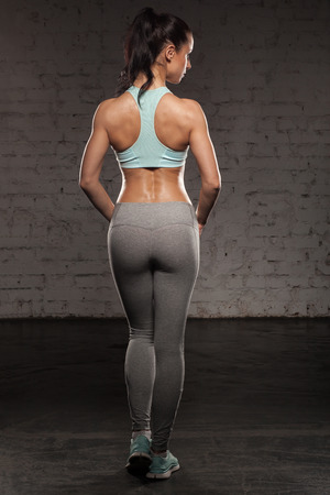 girl in sportswear: the back of sports women on training, fitness girl with muscular body, do her workout Stock Photo