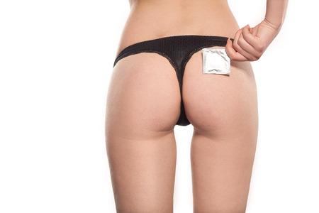mujer desnuda: Condón cerca culo sexual de la mujer hermosa joven, tanga negro, ropa interior hermosa, sexo seguro