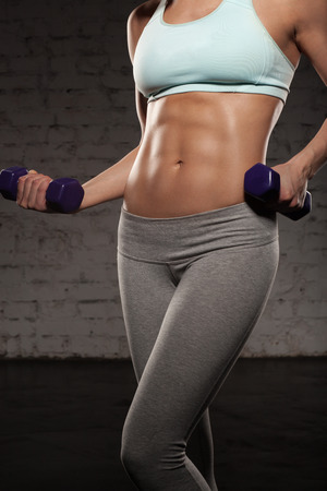 muscular body: Fitness female woman with muscular body, do her workout with dumbbells, abs, abdominals Stock Photo