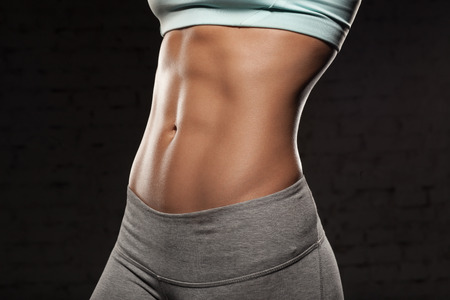 slim tummy: Fitness female woman with muscular body, do her workout, abs, abdominals Stock Photo