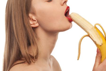 sex: роговой девушка ест и лижет банан. оральный секс Фото со стока