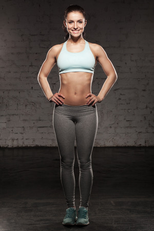 cuerpo femenino: Mujer deportiva con una hermosa sonrisa, mujer de fitness con cuerpo musculoso, hacer sus ejercicios, abdominales Foto de archivo