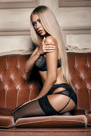 glamour nude: sexy woman in seductive black lingerie sitting on a couch in stockings