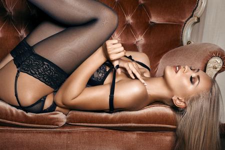 hot breast: сексуальная женщина в черном белье соблазнительной лежа на диване в чулках Фото со стока