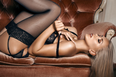 erotic breast: sexy woman in seductive black lingerie lying on a couch in stockings