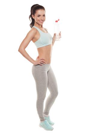 dieta sana: Muchacha deportiva beber agua de una botella después de un entrenamiento, entrenamiento físico, aislado en fondo blanco Foto de archivo