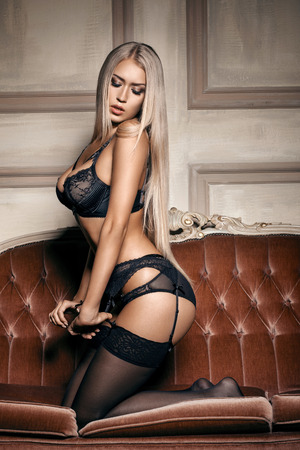 donna nuda: donna sexy in lingerie nera seducente seduto su un divano in calze