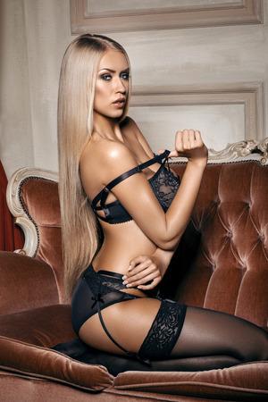 sexy nackte frau: sexy Frau in verführerische schwarzen Dessous sitzt auf einer Couch in Strümpfen